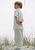 Kleiner Junge am Strand hält Blume auf dem Rücken