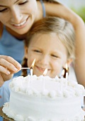 Mother lighting candles on birthday cake for daughter