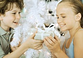 Boy handing girl christmas gift