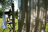 Curtain partially blocking view of chair with bathing utensils in garden