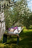Relaxing in hammock with cushions in Mediterranean garden