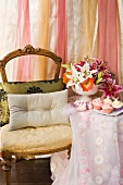 Cushions on antique chair next to side table with floor-length tablecloth and bouquet