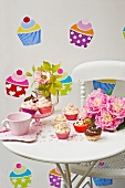 Cakes in colourful cases on side table against wall with cake-themed wall stickers