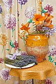 Flowers in rustic ceramic vase on side table in front of floral curtain