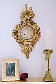 Lit candle in brass candlestick on surface and gilt-framed wall clock on pastel wall