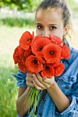 Girl with bunch of poppies