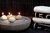 Relaxation in spa - lit pebble candles in stone dish next to stacked towels