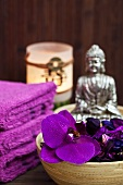 Meditative atmosphere in spa - violet orchid flowers in bamboo dish with Buddha figurine in background