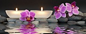 Relaxation in spa - tea lights and orchid flowers reflected in water