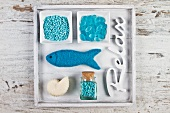 Maritime decoration with turquoise bath salts and bath pearls and a fish-shaped sponge