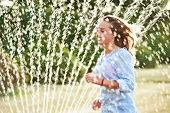 Young woman running through spray of a sprinkler