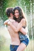 Couple hugging under sprinkler
