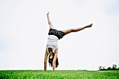 Teenager doing a handstand on a lawn