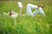 Woman lying in long grass with book