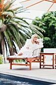 Woman in dressing gown relaxing by pool
