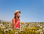 Woman puffing on a dandelion clock