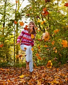 Woman jumping in autumn leaves