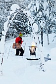 Woman carrying picnic hamper towards fire basket in snowy garden