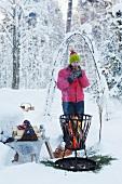 Woman drinking coffee next to fire basket in snowy garden