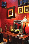 Framed pictures above console table against brick wall painted red