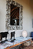 Mirror with silver, ornamental frame above African cattle ornaments on console table