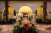 Innenhof mit tropischen Pflanzen und Blick in möblierten Arkadenraum mit offenem Kamin