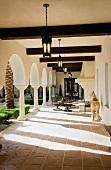 Möblierte Veranda einer herrschaftlichen Villa mit Blick durch Arkaden in Innenhof