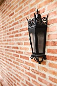 Italianate lantern style sconce on brick wall
