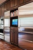 Stilmix in der Küche - Einbauschrank mit Kassettentüren aus dunklem Holz, unterbrochen von modernen Edelstahlfronten