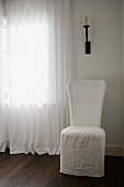 High back chair below candle sconce