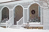 Front porch of shingle style home covered in snow