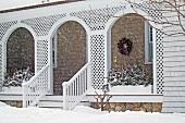 Schneetreiben vor der Veranda einer Villa mit Arkaden aus weissen Holzgittern
