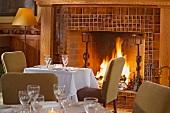Kleine, gedeckte Tische vor dem Kaminfeuer in ländlich gediegenem Speisezimmer