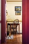 Blick durch offene Tür auf antiken Schreibtisch mit Stuhl