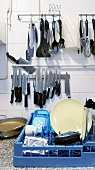 Various kitchen utensils hanging on the wall and a box of crockery in a commercial kitchen
