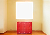 A red chest of drawers in front of a window in an otherwise empty room