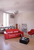 Glossy red leather couch and black coffee table on wooden floor in minimalist living room with retro atmosphere