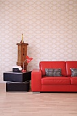 Partially visible glossy red leather couch next to table lamp on stacked floor cushions against op art wallpaper