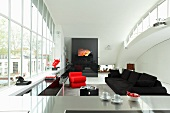 View across stainless steel kitchen counter to open-plan interior with black sofa and red designer armchair next to huge window