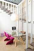 Simple glass table and chairs with pink upholstery in office with view of winding staircase