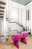 Simple glass table and chairs with pink upholstery below spherical pendant lamp in front of of winding staircase