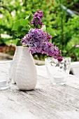 Violetter Flieder in Vase auf Gartentisch