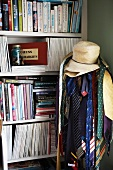 Ties and hats on clothes rack in front of bookcase