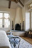 Kerzenständer um eingebauten Eckkamin und gepolsterte Sitzbank im Schlafzimmer eines Landhauses