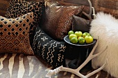 Decorative throw pillows antlers and apples on bed