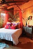 Bunte Kissen und weisse Tagesdecke auf Doppelbett neben antiker Kommode in afrikanischem Stil vor gelb getönter Wand