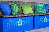Bright blue bench with decorative throw pillows and cushions