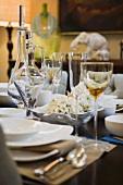 Weisses Gedeck auf Tischset und Weingläser mit Karaffe
