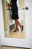 Reflection in mirror of woman getting ready for an evening out