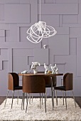 Modern pendant lamp above round dining table and wooden chairs with metal frames in front of wall with three-dimensional elements